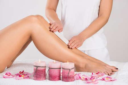 legs: Sección media de esteticista depilación pierna de la mujer en el salón