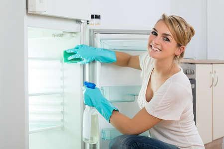 幸せな若い女を自宅の冷蔵庫を掃除の肖像画