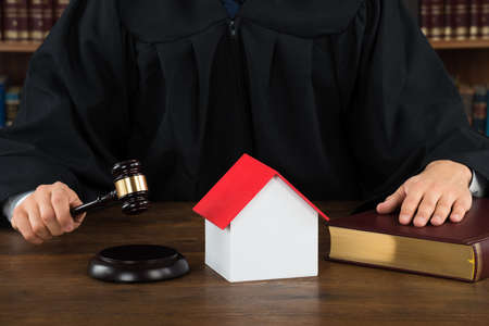 courtroom: Midsection of judge with house model hitting gavel at desk in courtroom Stock Photo