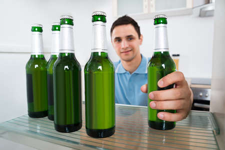 tomando refresco: Hombre joven sonriente que quitar la botella de cerveza de la nevera en casa Foto de archivo