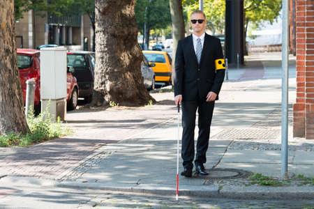 맹인을 입고 지팡이를 들고 보도에서 걷는 맹인
