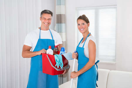 cleaning services: Two Happy Professional Cleaners With Cleaning Equipments At Home Stock Photo