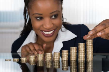 businesswoman: Close-up Of A Smiling African Businesswoman Making Stack Of Coins Stock Photo