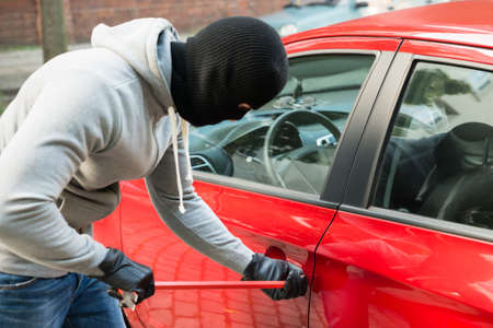 Thief With Mask Trying To Open Cars Door By Using Crowbar