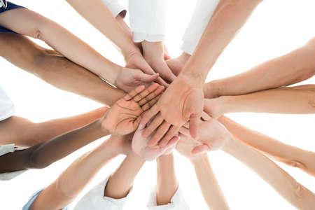 directly below: Directly below shot of medical team piling hands against white background