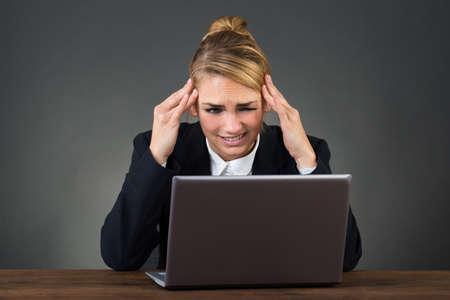 dolor de cabeza: empresaria joven que sufre de dolor de cabeza en el escritorio sobre fondo gris