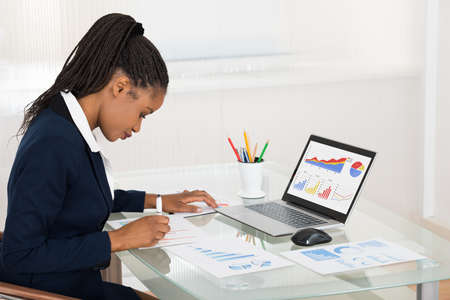 mujeres africanas: Empresaria africana joven que analiza el gráfico Mientras computadora portátil en el escritorio de oficina