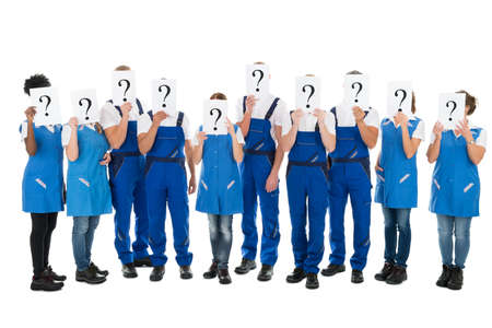 Cleaning team: Full length of janitors hiding faces with question mark signs against white background
