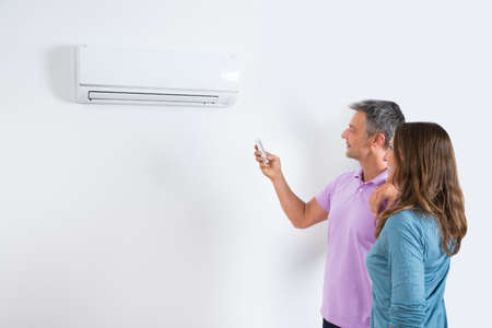 couple home: Mature Couple Standing In Front Of Air Conditioner And Adjusting The Temperature By Remote Stock Photo