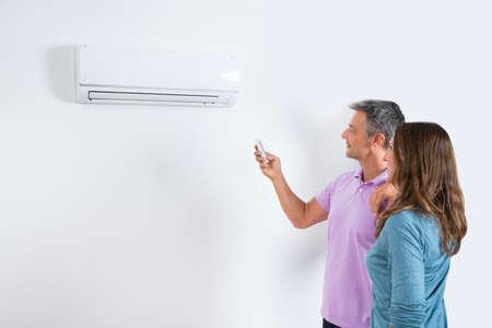 pareja en casa: Pareja madura se coloca delante del acondicionador de aire y ajuste de la temperatura Por Remoto