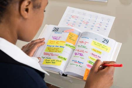 Close-up Van Zakenvrouw Schrijven Schema In Kalender Dagboek