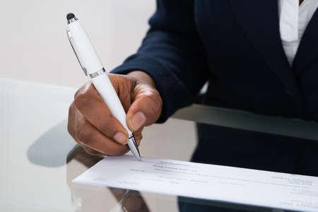 小切手に署名人の手のクローズ アップ 写真素材