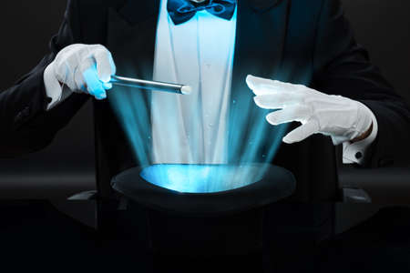 midsection: Midsection of magician holding magic wand over illuminated hat against black background