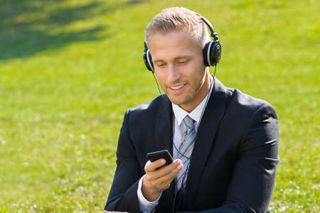 people relaxing: Young Smiling Businessman Sitting On Grass Listening Music In Park Stock Photo