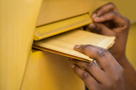delivery box: Close-up Of A Persons Hand Inserting Letter In Mailbox