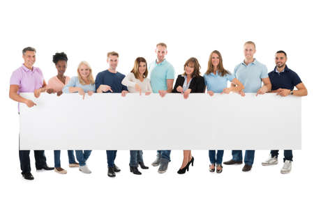 Full length portrait of confident creative business team holding blank billboard against white background Foto de archivo