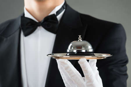 service bell: Midsection of waiter holding service bell in plate against gray background Stock Photo