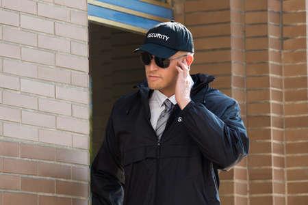 guardia de seguridad: Primer De La Guardia de seguridad se coloca delante de la entrada escuchando el auricular Foto de archivo