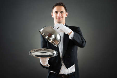 hospitality staff: Portrait of happy waiter holding cloche over empty tray while standing against gray background