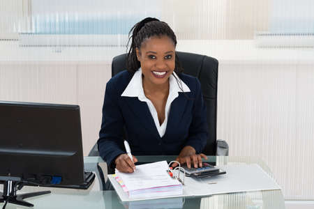 relaxed woman: Smiling African Businesswoman Calculating Bills At Office Desk Stock Photo