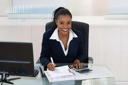 schwarz: Smiling African Geschäftsrechenrechnungen am Büro-Schreibtisch