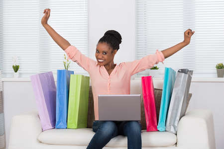 online purchase: Young African Excited Woman While Shopping Online On Laptop