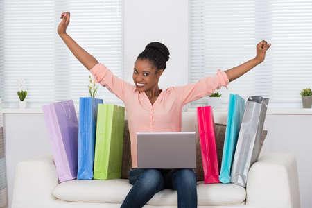 vzrušený: Young African rozrušená žena sice Nakupování na internetu na notebooku