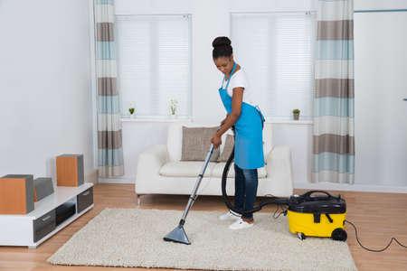 mujer limpiando: Joven mujer africana de limpieza de alfombras con aspiradora Foto de archivo
