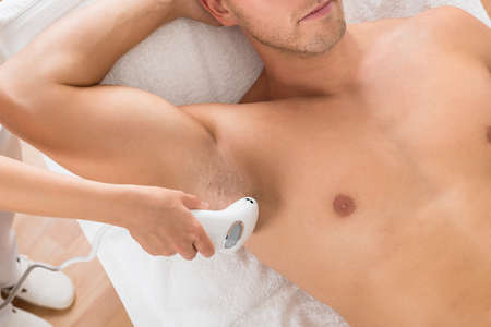 depilation: High Angle View Of Beautician Giving Laser Epilation Treatment On Mans Armpit