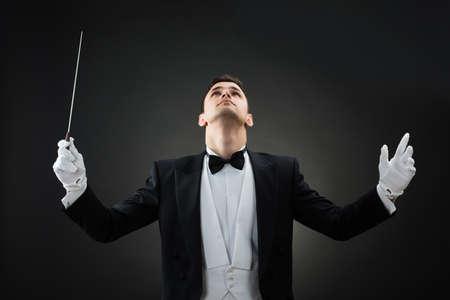 orquesta: Joven conductor de la música masculina mirando hacia arriba mientras sostiene el bastón contra el fondo gris