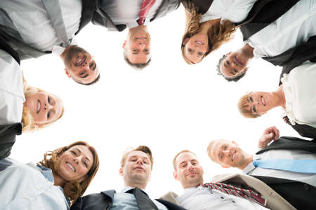Directly below portrait of confident business team standing in huddle against white background