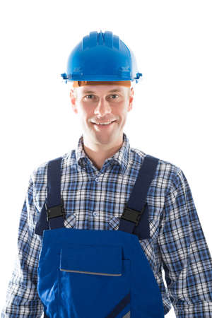 front view: Portrait of smiling mid adult construction worker standing against white background
