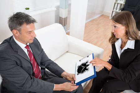 evaluating: Female Psychologist Showing Rorschach Inkblot Picture To Patient At Home