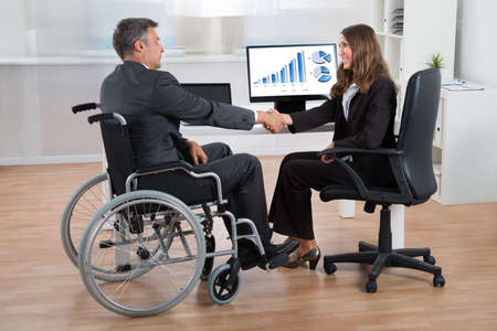 wheelchair access: Happy Businesswoman Shaking Hands With Disabled Businessman In Office Stock Photo