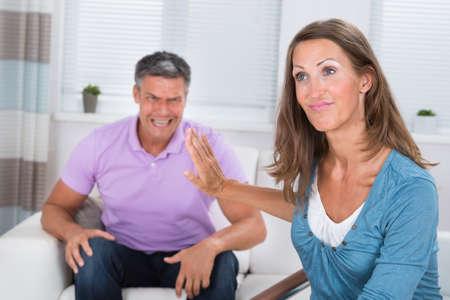 personas discutiendo: Angry hombre maduro Gritar a su esposa en la sala de estar Foto de archivo