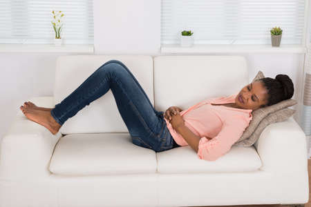 barefoot women: Young African Woman Lying On Sofa Suffering From Stomach Ache