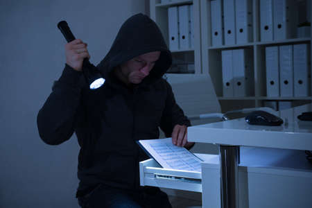 Robber with flashlight searching for documents in drawer at office