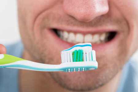 tooth whitening: Closeup of mid adult man brushing teeth