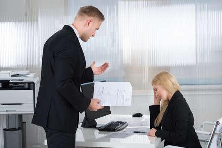 Jonge onderneemster schreeuwen tegen vrouwelijke werknemer aan de balie in het kantoor