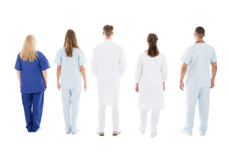 white man: Full length rear view of medical professionals standing against white background