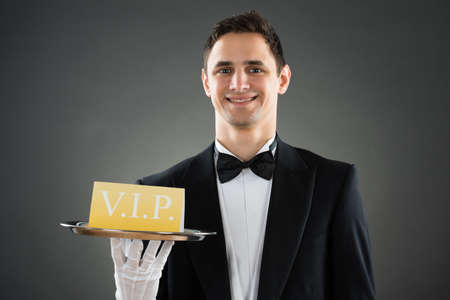 hospitality staff: Portrait of happy young waiter holding tray with VIP sign against gray background