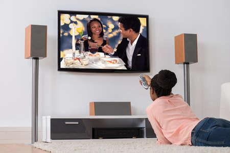 mujer viendo tv: Mujer africana joven que miente en la alfombra Televisión de observación