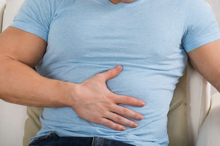 man stomach ache: Midsection of man with stomach ache sitting on couch at home