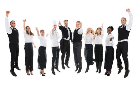 hospitality industry: Full length portrait of happy restaurant staff celebrating success against white background