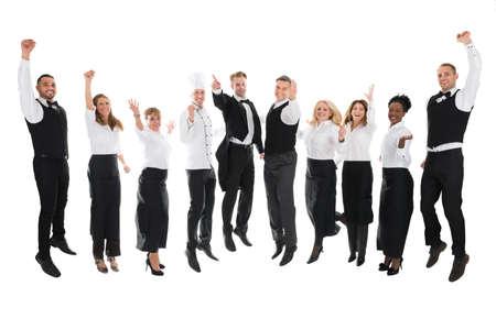 hospitality staff: Full length portrait of happy restaurant staff celebrating success against white background