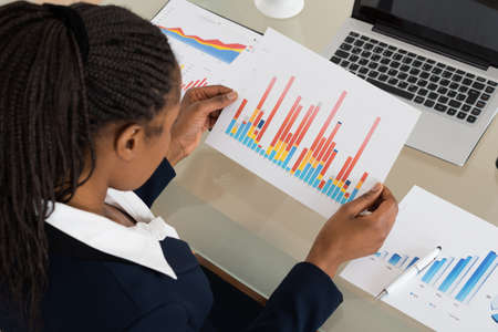 Young African Businesswoman Analyzing Colorful Bar Graph At Office Desk