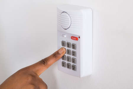 emergency number: Close-up Of Persons Hand Pressing Button On Security System