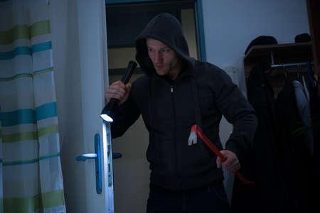 Mitte der erwachsenen Räuber mit Brechstange und Taschenlampe in Haus betreten
