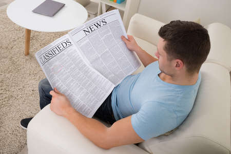 classifieds: High angle view of mid adult man reading newspaper on sofa at home