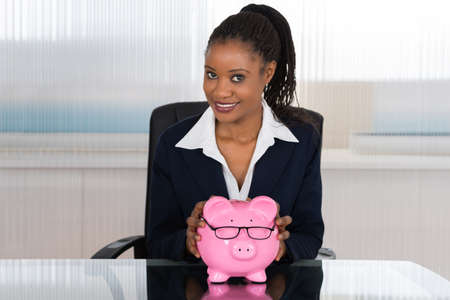 piggy: Young African Businesswoman Holding Piggybank At Office Desk Stock Photo
